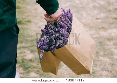 Close up on man's hand carrying two brown paper bags of fresh cut lavender from pick you own lavender farm