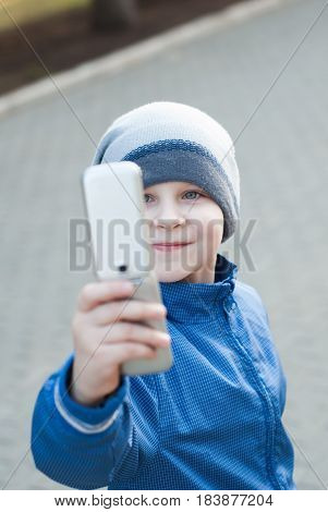 kid taking selfie with mobile phone, the little boy in the hat, walk in the open air