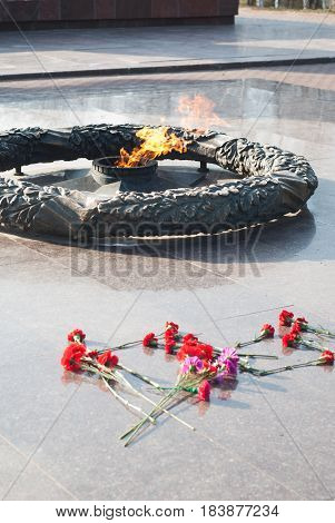 Eternal flame in honor of the fallen Soviet soldiers during the Second world war, red carnations