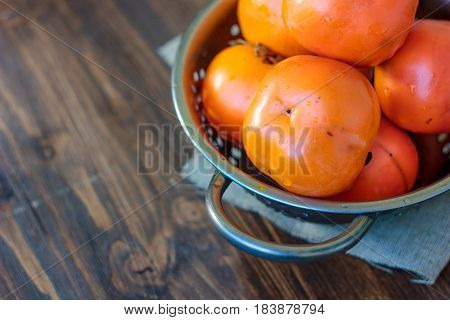 Persimmons In Metal Collander On Wooden Table.