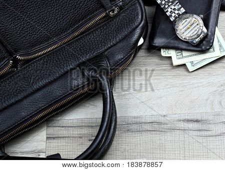 Man accessories in business style, leather briefcase, blackwallets with money and watch.Copy space