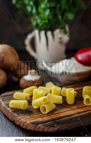 Raw Italian rigatoni pasta on wooden kitchen board