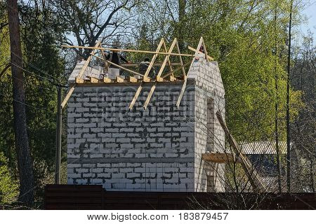 The construction of a private white house over the fence from the builders on the roof
