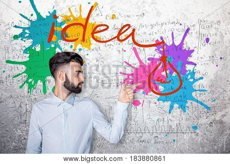 Young businessman pointing at clorful splashes on concrete background with mathematical formulas. Creative idea concept