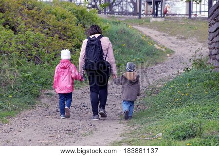 Woman with backpack leads two children's hands