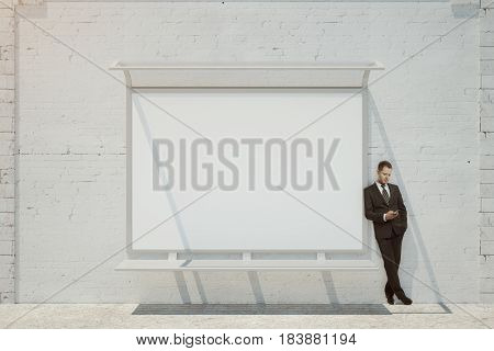 Businessman with smartphone leaning on brick building with empty whiteboard. Advertisement concept. Mock up 3D Rendering