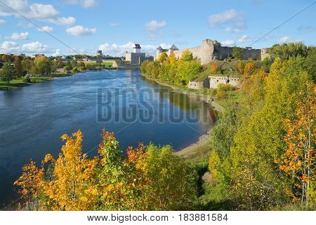 Golden Autumn on the border river Narva. View of the Russian Ivangorod fortress and the Estonian castle of Herman. The border between Estonia and Russia