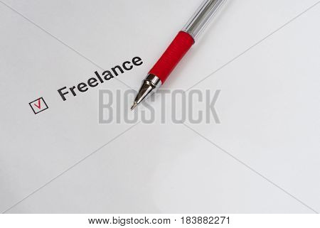 Questionnaire. Red pen and the inscription Freelance with check mark on the white paper