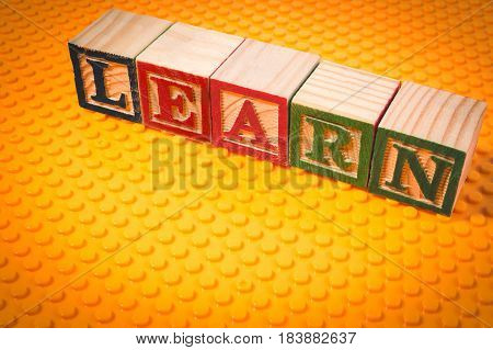 Learn Word Written In Wooden Cube On Yelllow Plastic Brick Plate With Yellow Light Effect For Backgr