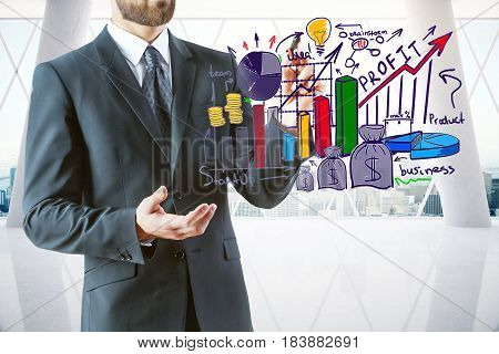 Young businessman in modern interior with city view holding abstract colorful business sketch. Profit concept. 3D Rendering