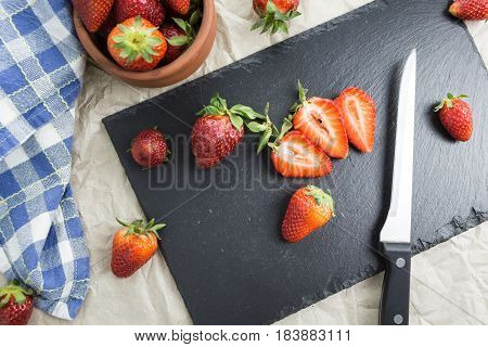 Red Ripe Strawberries  On A Table Some Sliced And A Knife