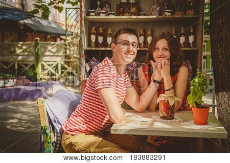 Young Beautiful Happy Loving Couple Sitting At Street Open-air Cafe Holding Hands. Beginning Of Love