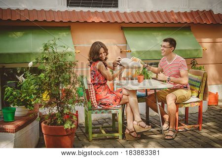 Young Funny Happy Loving Couple Sitting At Street Open-air Cafe And Fighting With Pillows Outdoors.