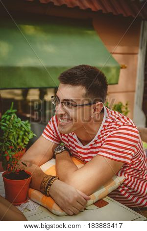 Young handsome smiling man in white and red striped T-shirt sitting and relaxing at street open-air cafe. Lifestyle concept