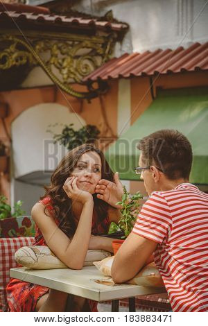 Young Beautiful Happy Loving Couple Sitting At Street Open-air Cafe Looking At Each Other. Beginning