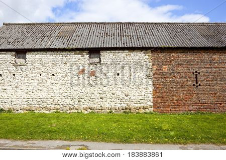 an old rustic barn made from white stone and orange brick with windows and wooden shutters on a grassy bank