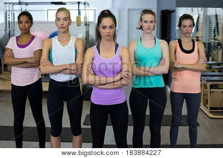 Portrait of confident women standing with arms crossed in gym