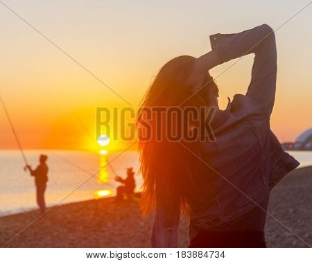 Young attractive woman on the beach at sunset time in backlight scene with fishermen on background