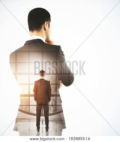 Back view of thoughtful young businessman in interior with city view and copy space. Future concept. Double exposure