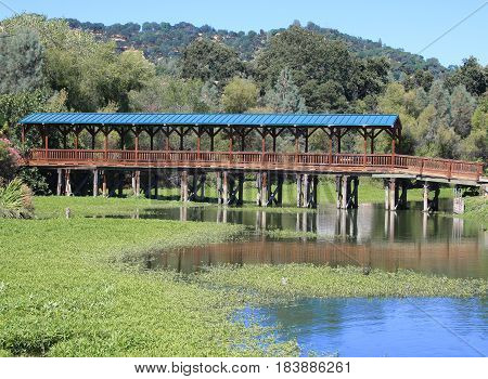 Covered long bridge above a lake with water plants and a mountain range in the distance