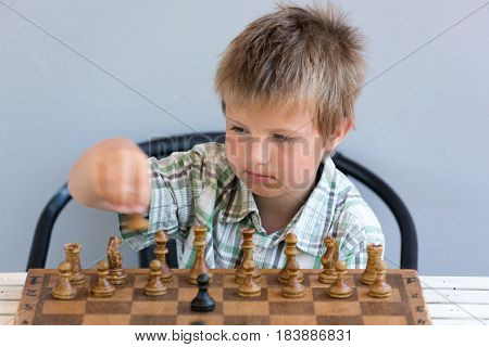 A Little clever boy thinking about chess