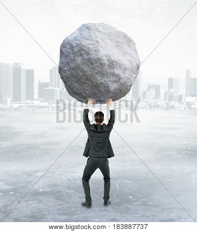 Back view of young businessman holding huge rock on abstract background. Burden concept