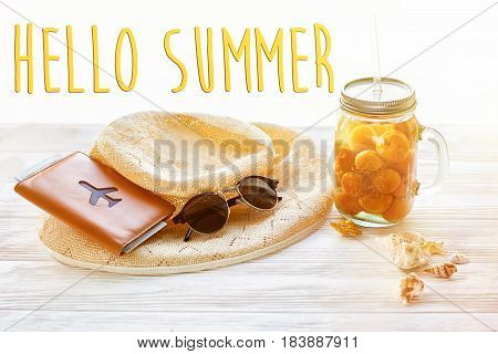 Hello Summer Text On Yellow Cocktail Juice With Apricot, Hat, Sunglasses And Shells And Passport On