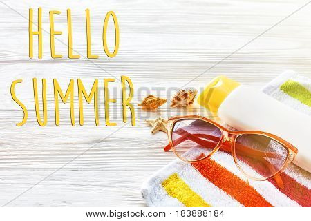 Hello Summer Text On Colorful Towel, Sunglasses, Yellow Sunscreen And Star Shells On White Rustic Wo