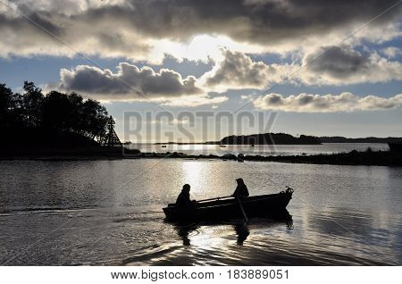 in the evening two fishermen in a boat floating on the night bite White sea Russia