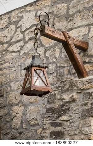 Old lantern hanging on the stone wall detail