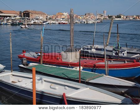 Chioggia, Italy. Lagoon with boats. A motorboat walks in the water.