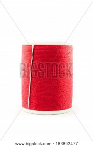 Spool Of Red Thread And Needle On White Background