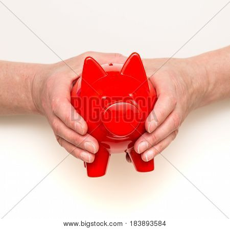 Womans hands holding a red piggy bank