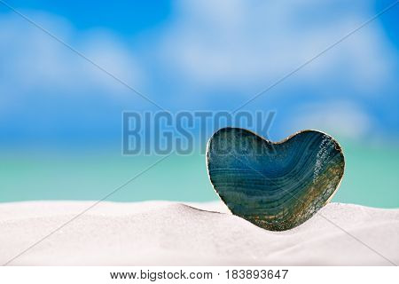 green glass heart on white sand beach,ocean,  sky and seascape
