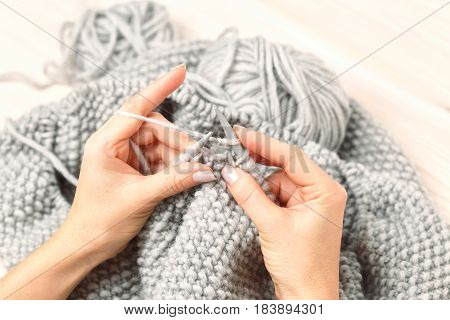 Close-up of hands knitting craft. handmade. Knitting with knitting needles of thick yarn.