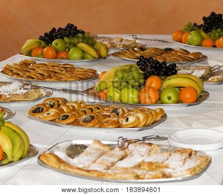 Snacks, cakes and fruit prepared for party