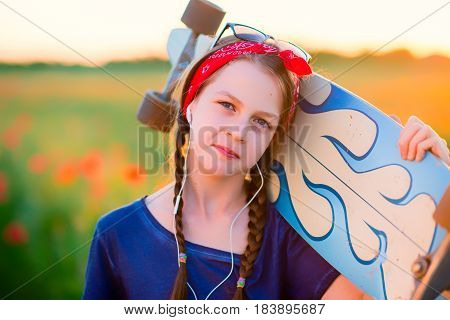Young hipster girl with braids in sunglasses and a red sash on her head listening to music with a longboard on her shoulders - against a summer meadow at sunset