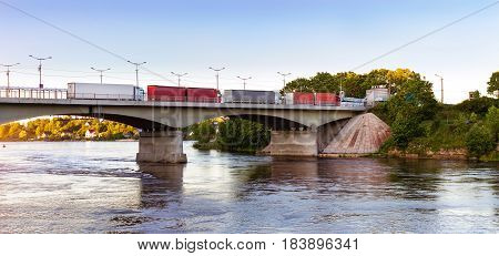 Heavy trucks with trailers are in queue on bridge on Russian-Estonian state transport-walking border. Reinforced concrete pontoon bridge over Narva river. Russia Ivangorod