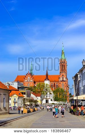 Bialystok Poland - April 29 2012: Tourists walk in sunny summer day on pavers central square of Kosciusko Market. On background Cathedral Basilica of Assumption of Blessed Virgin Mary in Bialystok