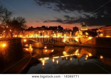 View on Tiber river and night illuminated Vatican city at evening from Saint Angel Bridge in Rome, Italy.