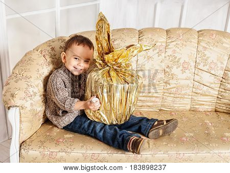Boy blonde sitting on a classic couch smiling and holding a big gift