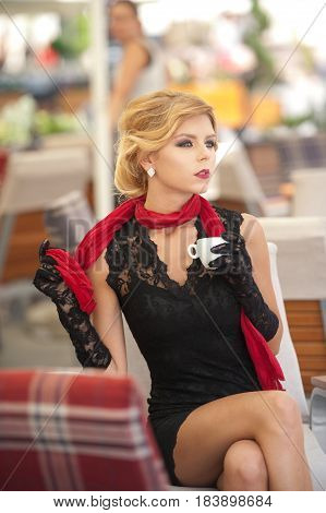Fashionable attractive lady with little black dress and red scarf sitting on chair in restaurant and drinking coffee. Short hair blonde woman with makeup and creative haircut holding a cup of coffee