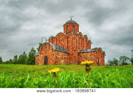 Architecture summer cloudy landscape - Church of the Transfiguration of Savior on Kovalevo in Veliky Novgorod Russia. Focus at the church. Architecture landscape with dandelions on the foreground.