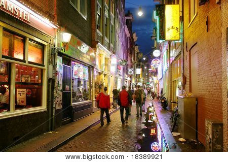 Bars and coffee shops on the street full of tourists at night in famous Red Light District in Amsterdam, Netherlands.