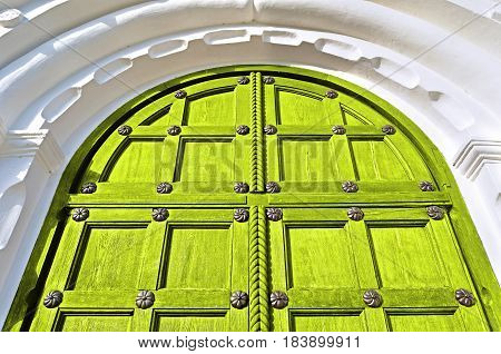 Architecture elements. Aged wooden door with metal rivets and architecture arch of white stone - architecture background