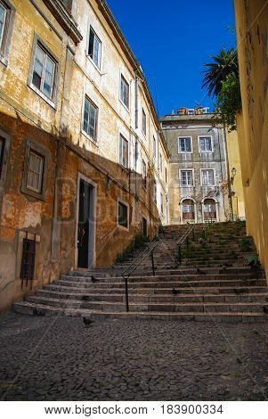 Steep stairs of Lisbon between historic building with rustic yellow facades
