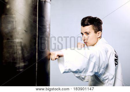 Girl In A White Kimono Beats Black Punching Bag On Grey Background. Of Tae Kwon Do, Karate, Kick