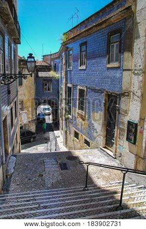 Steep stairs of Lisbon between historic buildings with rustic facades covered with tiles