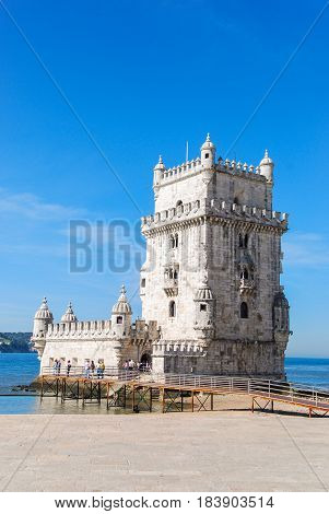 Belem tower in Lisbon, Portugal isolated with tourists in front and Atlantic ocean in the background