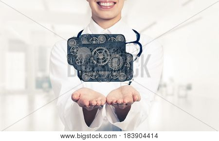 Close of woman doctor holding in palms cloud of gear mechanism